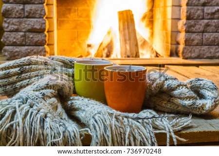 Two  mugs  for tea or coffee,  woolen things near  cozy fireplace, in country house, winter vacation, horizontal. #736970248