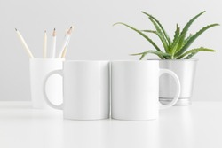 Two mugs mockup with workspace accessories and a succulent plant on a white table.