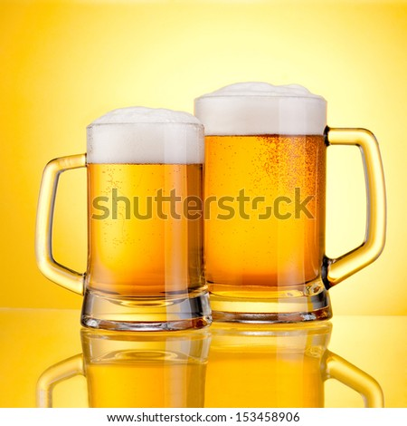 Two Mugs of fresh beer with cap of foam, isolated on yellow background
