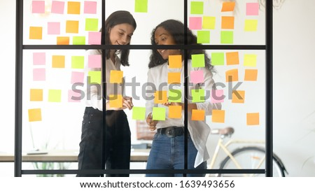 Two multi-ethnic affiliates girls hold group discussion produce fresh thoughts create new ideas writing on multi colored notes to-do list schedule, business team discuss project plan stock photo