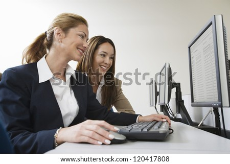 Two multi ethnic business colleagues working together on computer