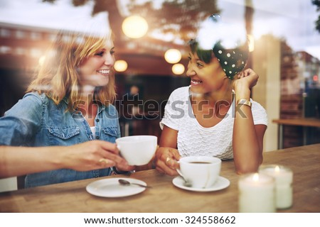 Two multi ethnic friends enjoying coffee together in a coffee shop viewed through glass with reflections as they sit at a table chatting and laughing #324558662