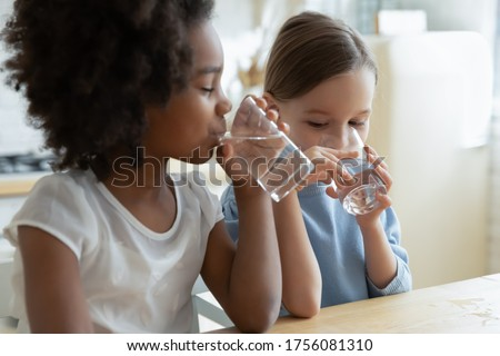Two multi racial little girls sit at table in kitchen feels thirsty drink clean still natural or mineral water close up image. Healthy life habit of kids, health benefit dehydration prevention concept Foto stock ©