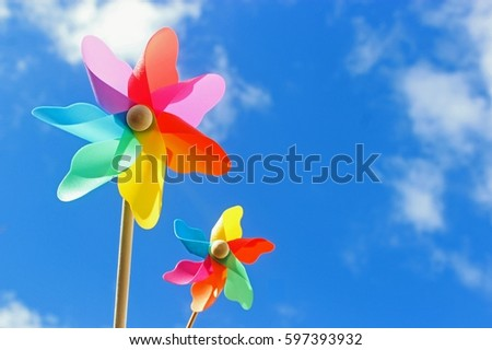 two multicolored pinwheels against blue sky  - Shutterstock ID 597393932