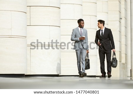 Two multiethnic business partners in formal clothing carrying bags and talking to each other they finished to work and walking along the street in the city