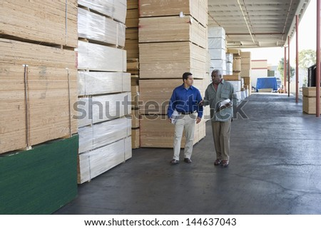 Two multiethnic men with clipboards walking along stacks of wood in warehouse