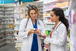 Two multiethnic pharmacists checking inventory at hospital pharmacy. Medical staff working in drugstore. Mature woman pharmacist with african colleague holding cough syrup and medicines.