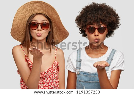 Two multiethnic sisters blow airkiss at camera, wears trendy shades, summer clothing, express love or say goodbye on distance, pose against white background. People, style and diversity concept