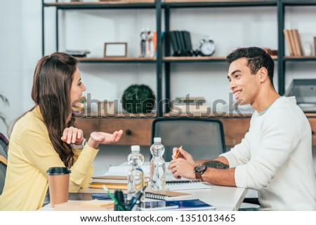 Two multiethnic students sitting at desk with books and studying together
