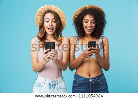 Two multiethnic summer women wearing straw hats expressing excitement or surprise while both using cell phones isolated over blue background