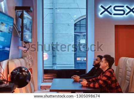 Two multiracial friends, enjoying spending time, playing in a multiplayer video game on a game console in a gaming club or internet cafe. #1305098674