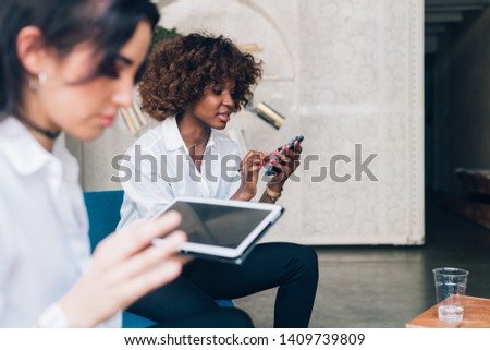 two multiracial young women working with digital device in modern office – freelance, interaction,  technology Stock photo ©