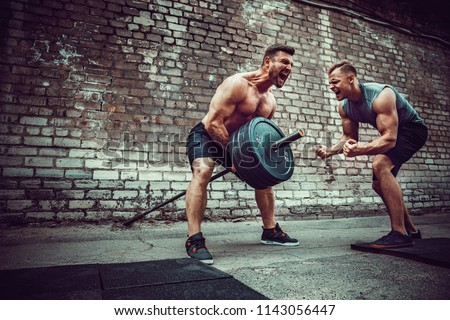 Two muscular athletes training, one raise the bar when other is motivating. Scream. Working hard. Street gym. Exercise for the muscles of the back