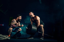 Two muscular bearded tattoed athletes training, one lift heavy weight bar when other is motivating. Scream. Working hard. Exercise for the muscles of the back