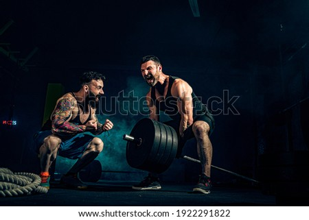 Two muscular bearded tattoed athletes training, one lift heavy weight bar when other is motivating. Scream. Working hard. Exercise for the muscles of the back Сток-фото ©