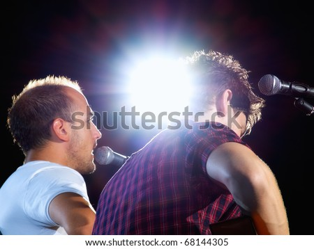 Two musicians on stage under the spotlight during the concert...