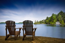 Two Muskoka chairs sitting on a wood dock facing a lake. Across the calm water is a white cottage nestled among green trees. There is a boat dock on the water in front of the cottage.