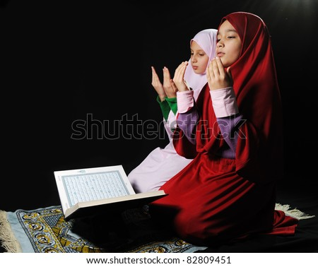 Two muslim girls with Holy Book Koran