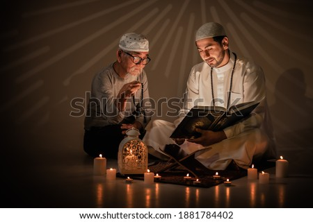 two muslim people read and study islam holy al quran book together during ramadan period. Al quran book with written arabic calligraphy meaning of Al Quran Stok fotoğraf ©