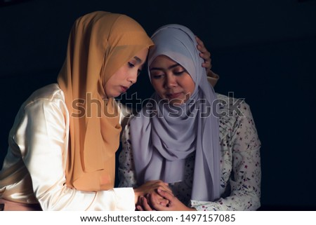 Two Muslim women wearing Muslim dress with hijab, sat solace in  in a dimly lit room.