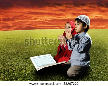 Two Muslims  children sitting on meadow in Ramadan and reading Koran and praying