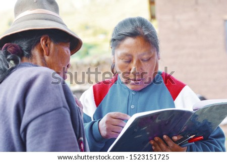 Two native american women holding a textbook. Education for adults.