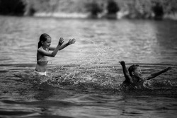 Two naughty little girls bathe in the lake. Black and white photo.