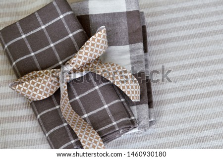 Two neat folded checkered taupe table napkins, with bow. Copy space, top view. Traditional relaxed dining at home concept. #1460930180