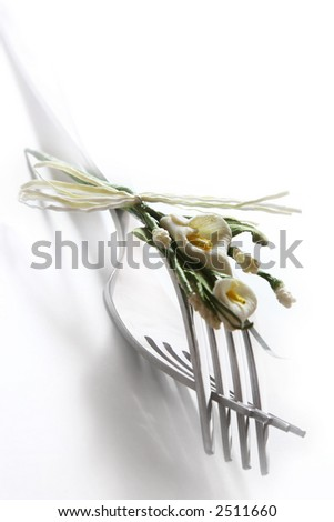 Two nestled forks decorated with a tiny flower bouquet