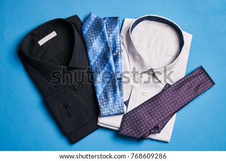 Two new colorful shirts with ties for men, on blue background, top view. Men's fashion #768609286