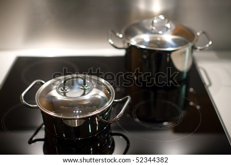 Two new stainless steel saucepans on modern kitchen range