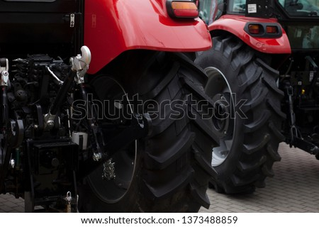Two new tractors at the fair of agricultural machinery.  Heavy agricultural machinery
