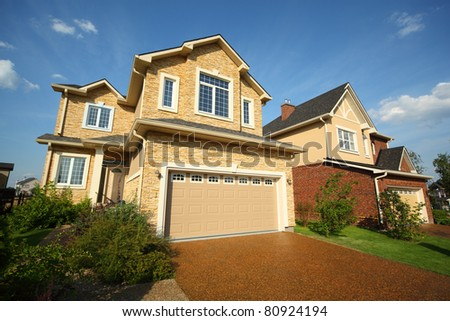 Two new two-storied beige stone and brick cottage with garage and garden.
