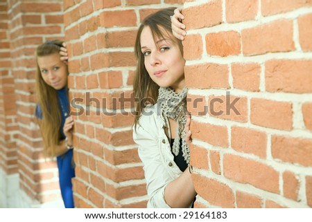 Two nice girls are looking out of the walls
