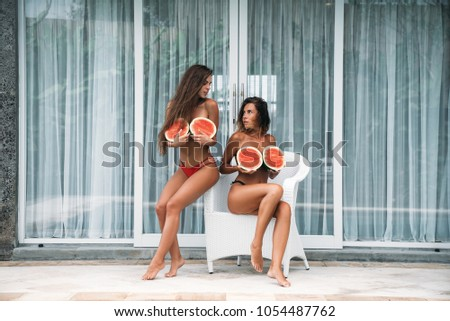 Two nice girls with curly hair holds a watermelon in their hands and covers breasts. Young woman in bikini sits on a white chair with fruit. The concept of healthy food and rest #1054487762