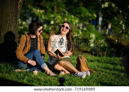 Two nice young women have coffee in the summer garden. Girlfriends sit on a grass and cheerfully talk in an environment of park greens.
