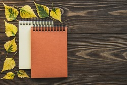 Two notepads in a frame of yellow leaves on a wooden background. Creative flat lay autumn composition. Mock up.