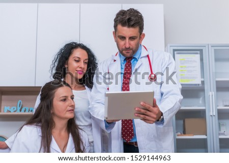 Two nurses, female physicians and a male doctor looking in a tablet at the doctor's office while discussing a medical report, patient's health problems.