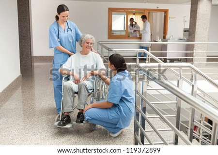 Two nurses talking with old women sitting in wheelchair and smiling