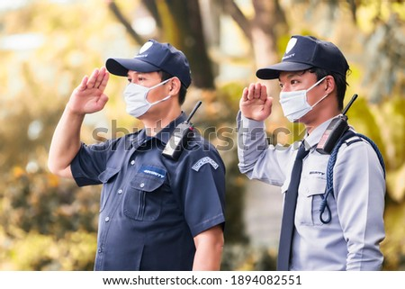 Two of Asian security guard make saluting entry entrance the village. Security Guard with mask, protect covid-19 warning. Guard check entrance to the village. Speed 15 limit in area, copy space.