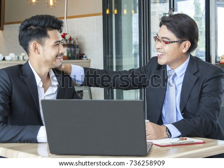 Two of business man sitting at the office desk. The older one is boss.The young one is subordinate. Subordinate presenting the work progress to his boss and the result is meet the boss's satisfaction.