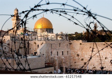 Two of Islam and Judaism's holiest sites, Jerusalem's Dome of the Rock and the Western Wall, seen through barbed wire.