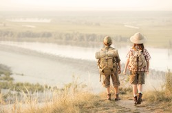 Two of little children, tourists looking into the distance on a high bluff at sunset on a summer evening