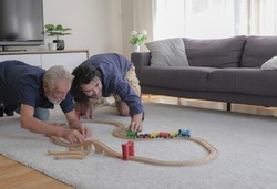 Two of old father and son are happy playing toy train together and makes them feeling childhood nostalgic in living room warmth house on holiday. Family's old times sake memories concept.