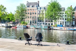 Two office chairs opposite the buildings in Amsterdam, Netherlands
