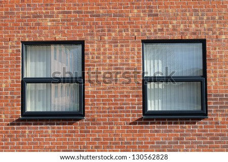 Two office windows in modern red brick office building.