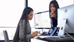 Two office woman work and discuss about business  in they office