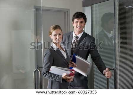 Two office workers in suits opening boardroom door