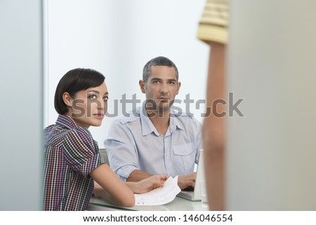 Two office workers looking up at cropped coworker standing in doorway
