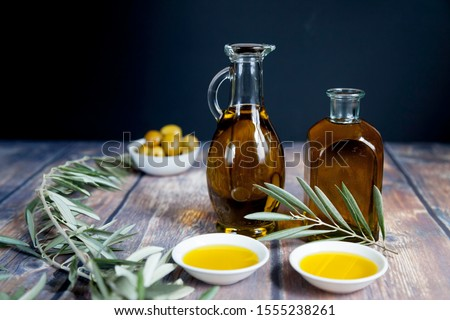two oil bottles, handful green olives in bowl, olive branch and two oil bowls on wooden table and black background